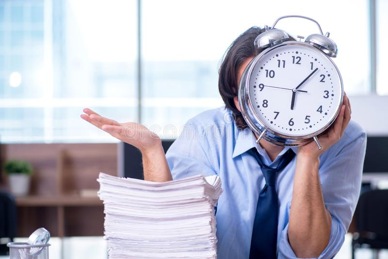 De jonge werknemer ongelukkig met het bovenmatige werk stock fotografie