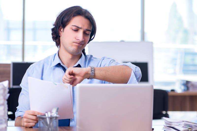 De jonge werknemer ongelukkig met het bovenmatige werk stock foto