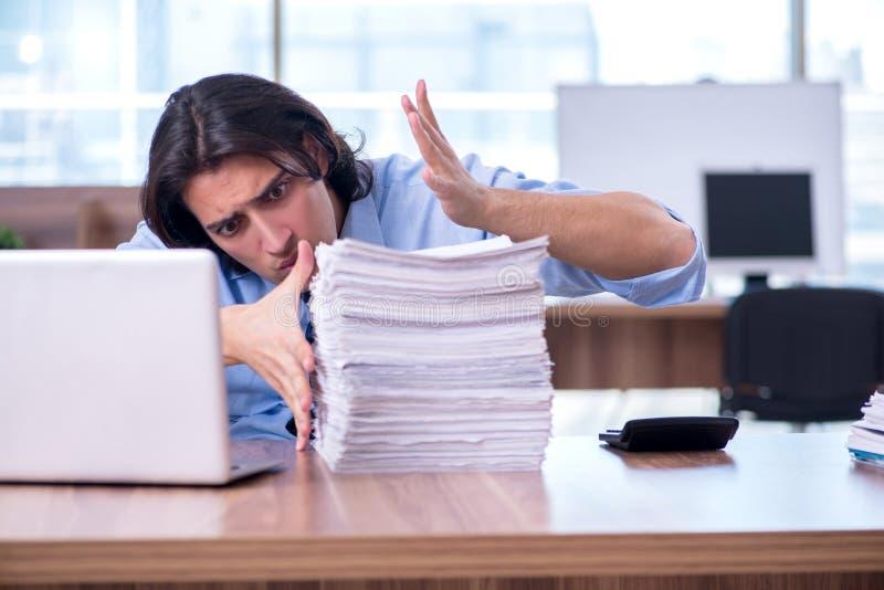 De jonge werknemer ongelukkig met het bovenmatige werk stock foto's