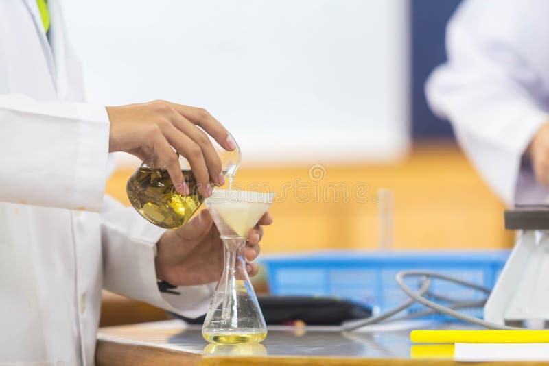 De jonge wetenschappers doen experimenten in wetenschapslaboratoria stock afbeeldingen