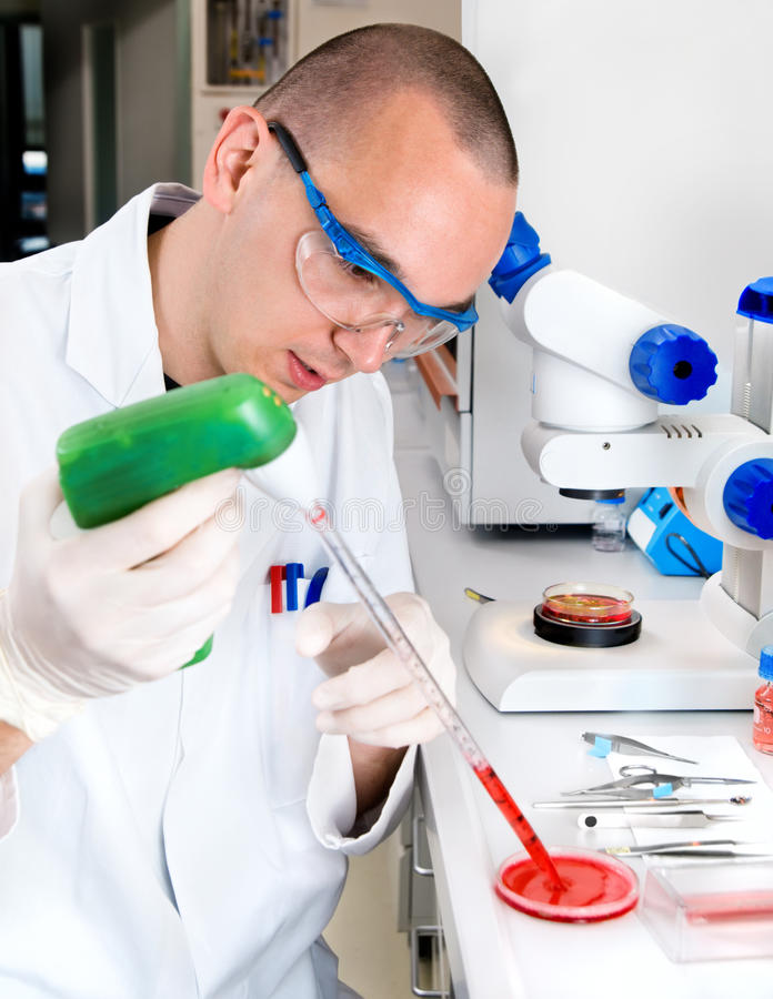 De jonge wetenschapperwerken in het laboratorium stock afbeeldingen