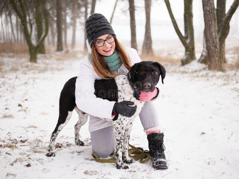 De jonge winter die van de vrouwen speelsneeuw in openlucht leuke goedgekeurde blinde zetterhond koesteren Vriendelijkheid en het stock afbeelding