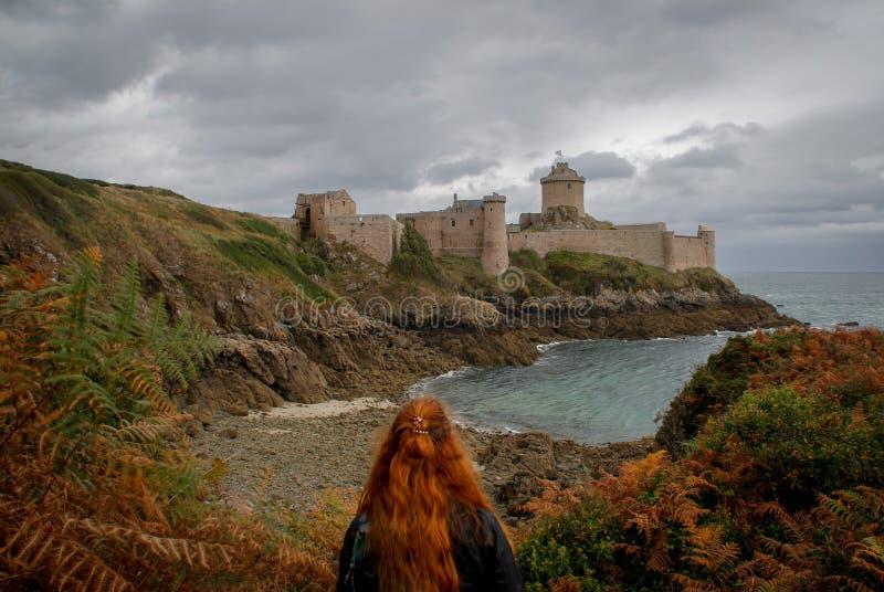 De jonge witte Kaukasische vrouw met lang rood haar bevindt zich tegen de achtergrond van beroemd middeleeuws kasteella Latte van royalty-vrije stock afbeeldingen