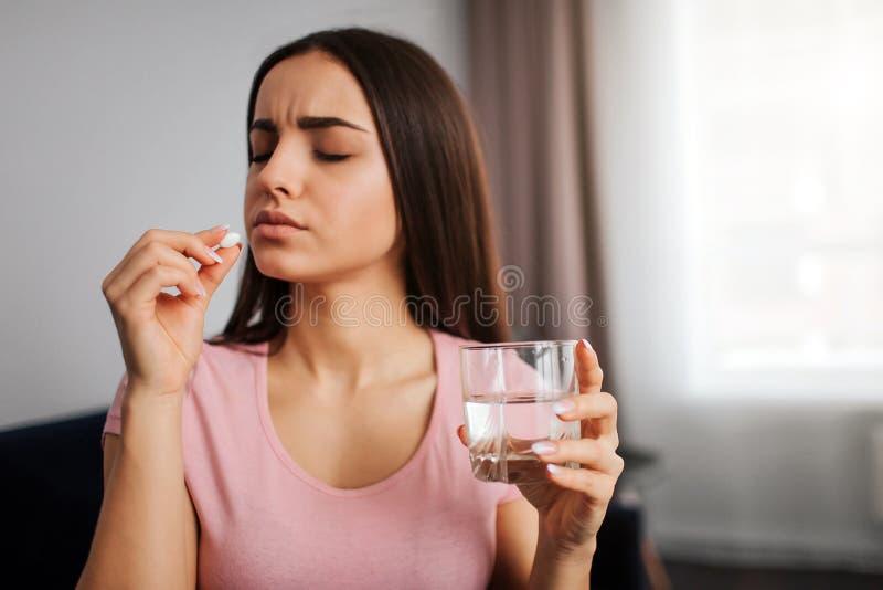 De jonge witte pil van de vrouwengreep ter beschikking Zij gaat het eten Modelgreepglas van waterinhand Zij kijkt verstoord en stock foto's