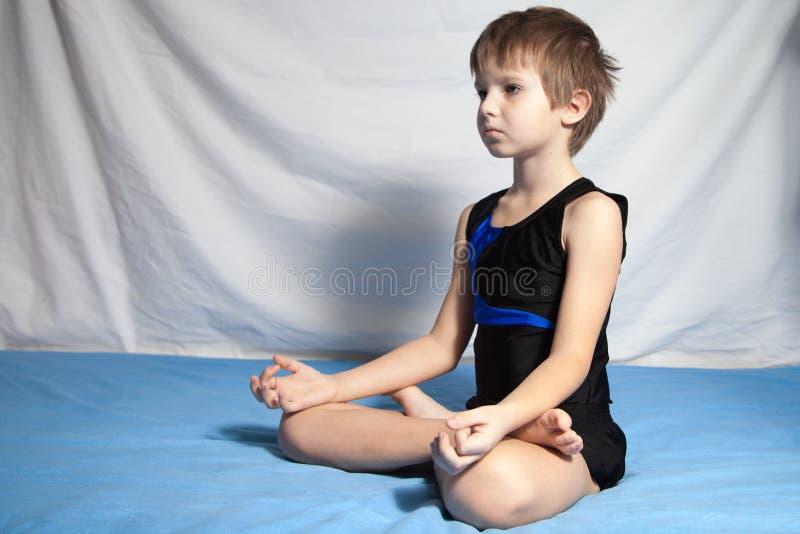 De jonge yoga van jongenspraktijken stock afbeeldingen