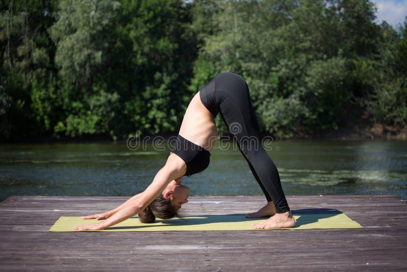 De jonge yoga van meisjespraktijken op de kust van het meer, het concept het genieten van van privacy en concentratie, zonlicht stock fotografie