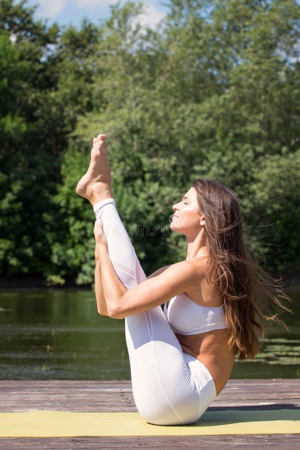 De jonge yoga van meisjespraktijken op de kust van het meer, het concept het genieten van van privacy en concentratie, zonlicht stock afbeeldingen