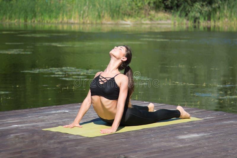 De jonge yoga van meisjespraktijken op de kust van het meer, het concept het genieten van van privacy en concentratie, zonlicht stock afbeelding