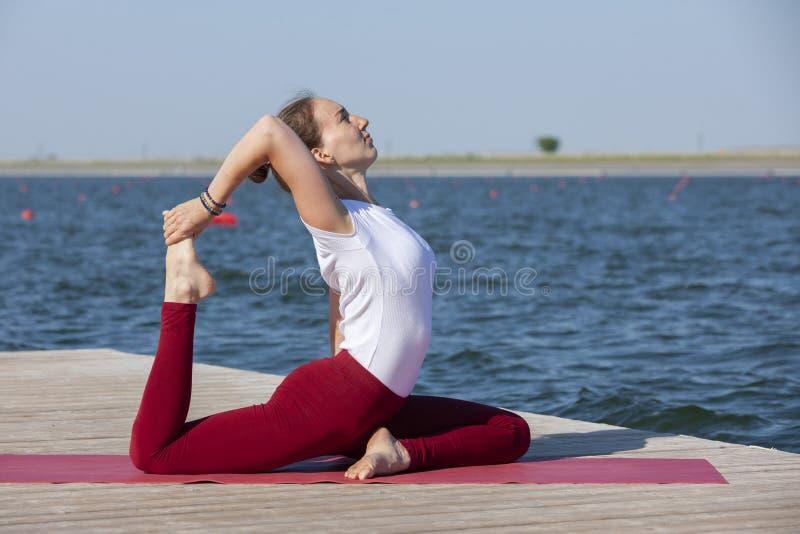De jonge yoga van meisjespraktijken op de kust van het meer, het concept het genieten van van privacy en concentratie, zonlicht stock foto