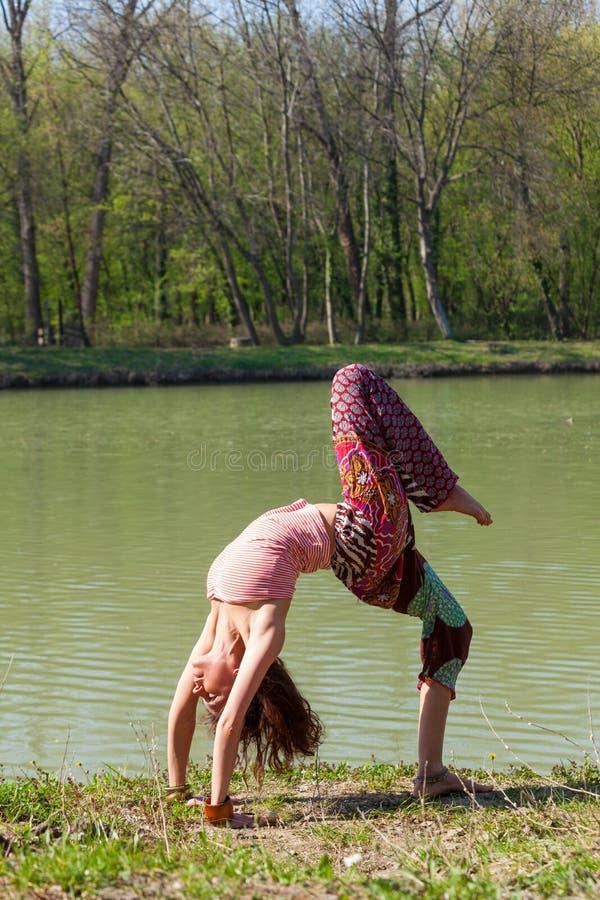 De jonge yoga van de vrouwenpraktijk openlucht door het schot van het het concepten volledige lichaam van de meer gezonde levenss royalty-vrije stock foto's