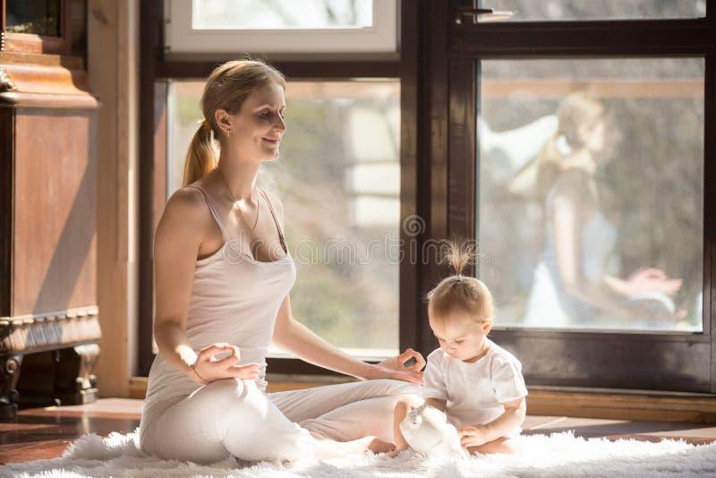 De jonge yogimoeder in Gemakkelijk Seat stelt dichtbij, babydochter stock foto's