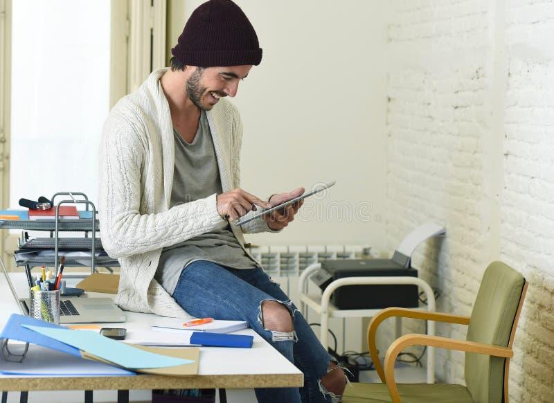 De jonge in zakenman in beanie en koele hipster informeel kijken zitting op huisbureau gebruikend digitaal gelukkig tabletstootku royalty-vrije stock foto's