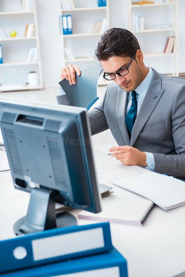 De jonge zakenman die bij zijn bureau werken royalty-vrije stock foto's