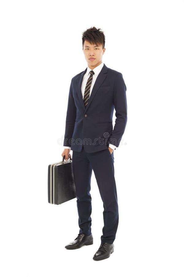 De jonge zakenman die een aktentas houden en dient zijn zak in stock foto's