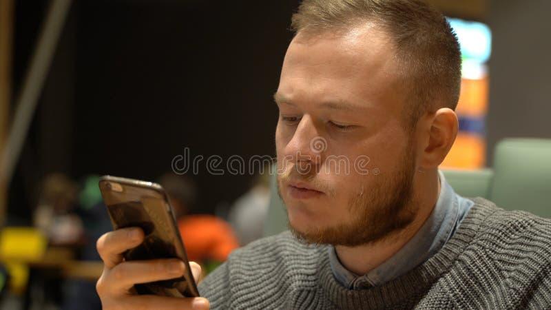 De jonge zakenman gebruikt sociale voorzien van een netwerktoepassing op zijn smartphone stock afbeeldingen