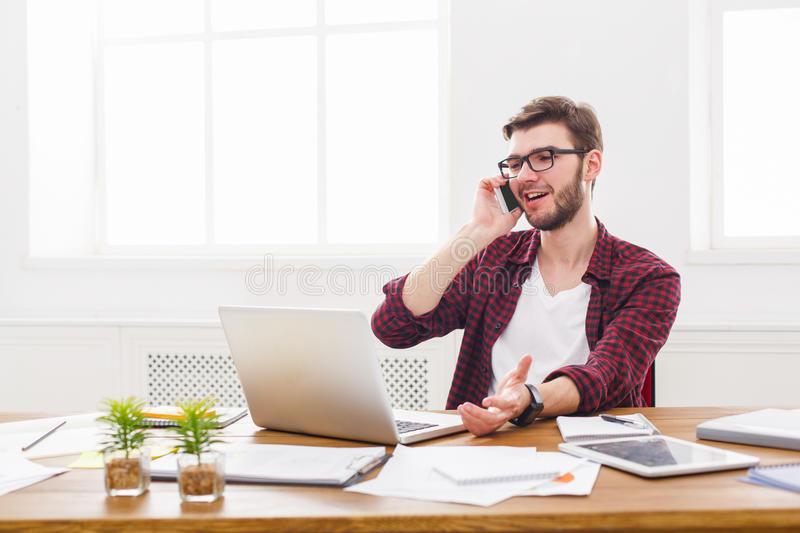 De jonge zakenman heeft een mobiele bespreking in modern wit bureau stock fotografie