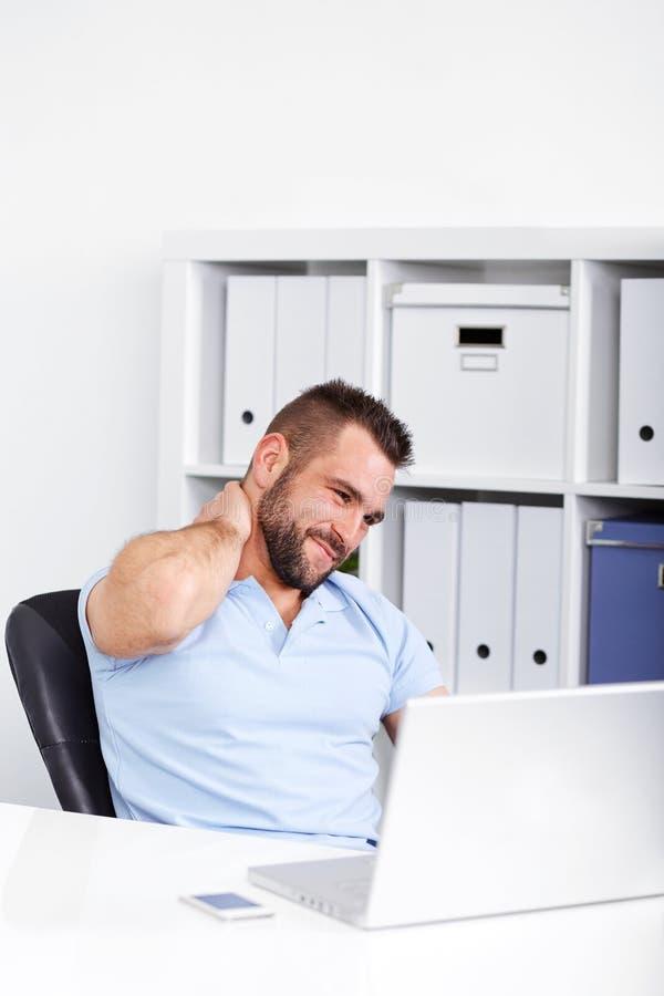 De jonge zakenman heeft pijn van cervicaal op het werk stock foto's