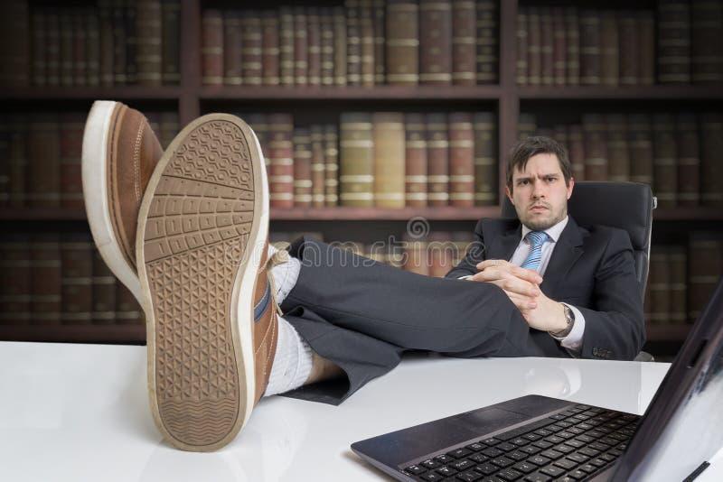 De jonge zakenman heeft voeten op bureau in bureau stock afbeeldingen