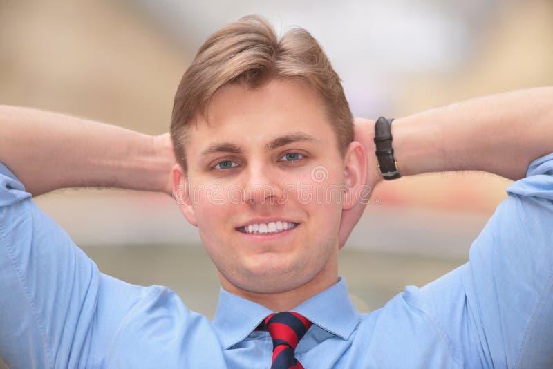 De jonge zakenman houdt handen achter hoofd royalty-vrije stock fotografie