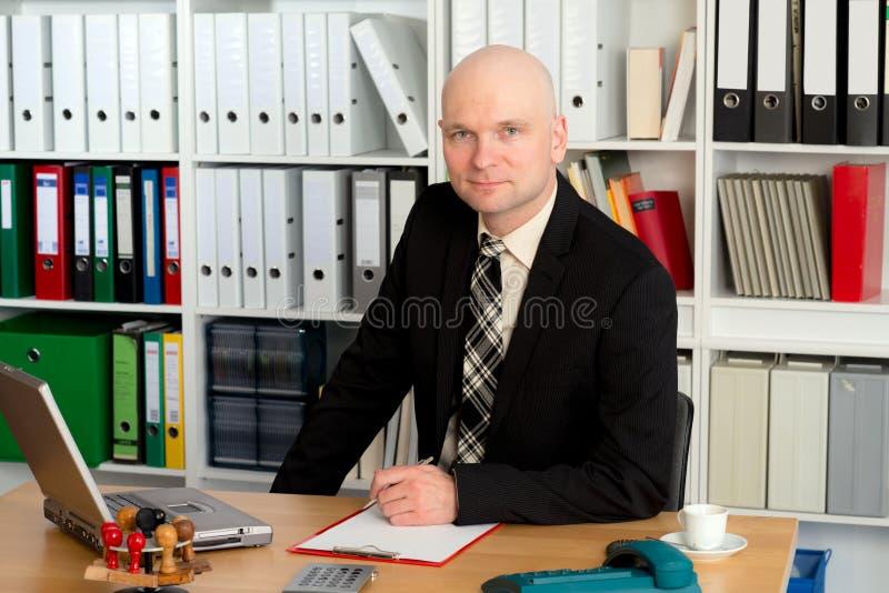 De jonge zakenman kijkt vriendschappelijk binnen aan de camera stock fotografie