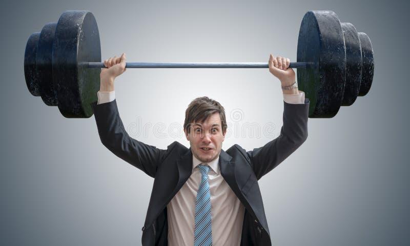 De jonge zakenman in kostuum heft zware gewichten op royalty-vrije stock foto's