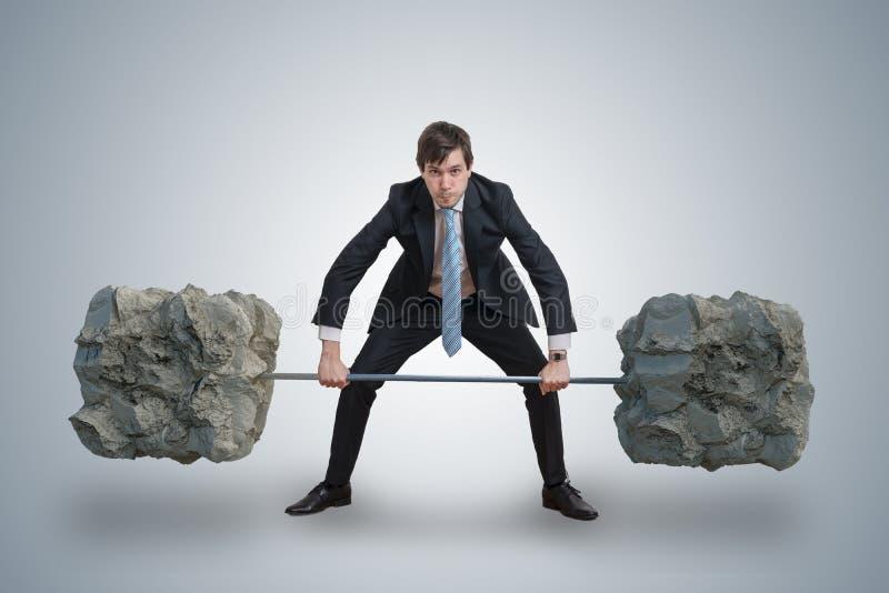 De jonge zakenman in kostuum heft zware gewichten op stock fotografie