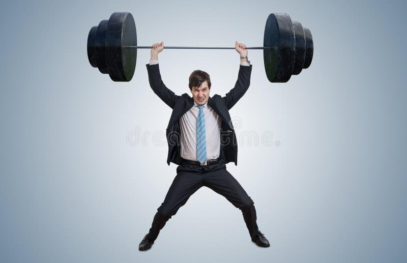 De jonge zakenman in kostuum heft zware gewichten op stock foto's