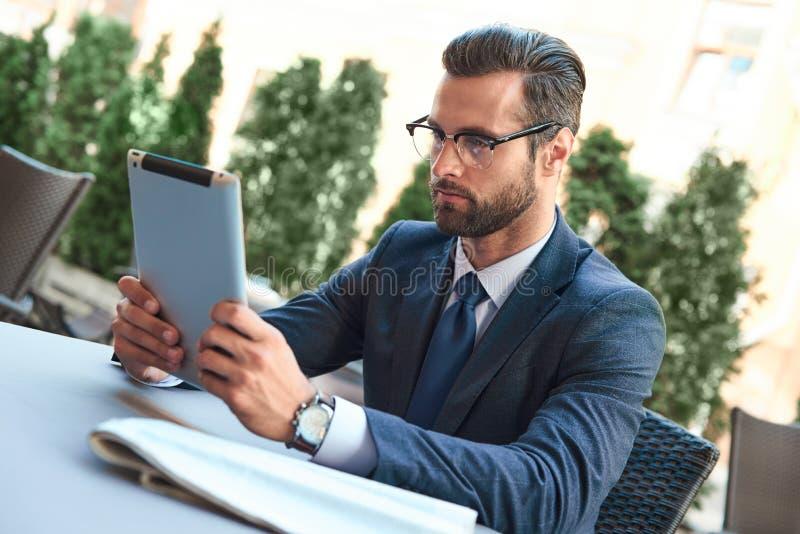 De jonge zakenman met een baard en het dragen van glazen zit en bekijkt de tablet stock foto's
