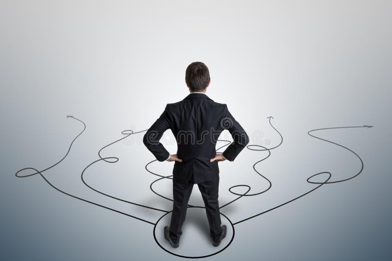 De jonge zakenman neemt besluit en selecteert strategie Mening van erachter stock afbeeldingen