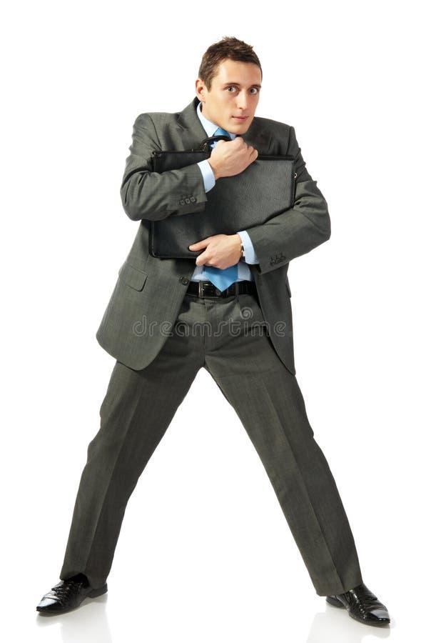 De jonge zakenman omhelst een portefeuille met vrees stock afbeeldingen