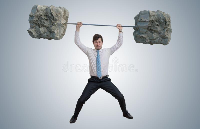 De jonge zakenman in overhemd heft zware gewichten op stock fotografie