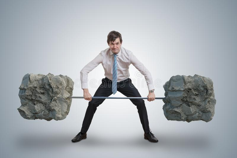 De jonge zakenman in overhemd heft zware gewichten op stock afbeeldingen