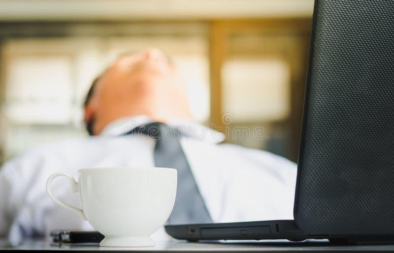 De jonge zakenman slaapt met laptop en een koffiekop op het bureau Zakenman die met slaperigheid op het werk worstelen royalty-vrije stock foto's