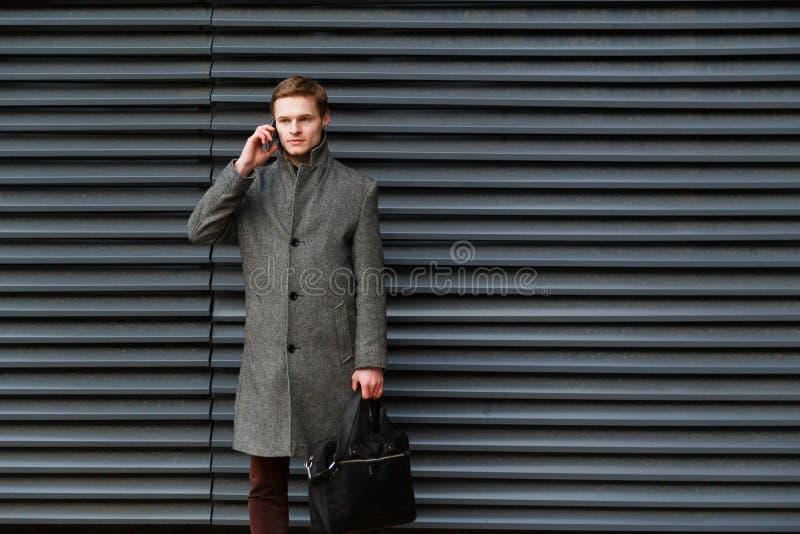 De jonge zekere zakenman in een grijze laag en een aktentas in zijn hand spreekt op mobiele telefoon tegen muur van modern stock foto's