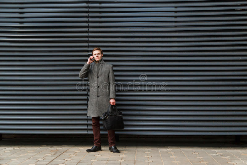 De jonge zekere zakenman in een grijze laag en een aktentas in zijn hand spreekt op mobiele telefoon tegen muur van modern royalty-vrije stock foto's
