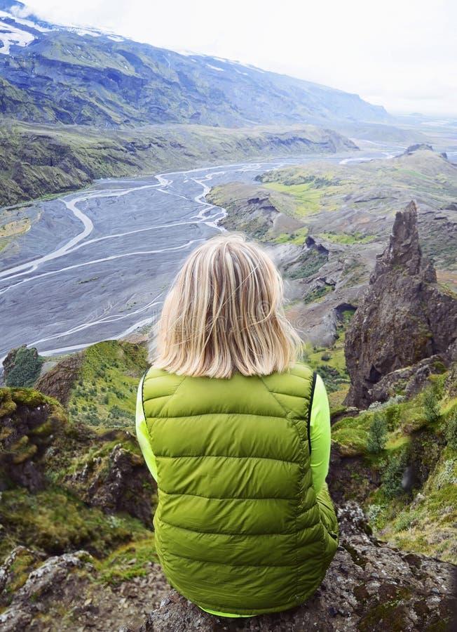 De jonge zitting van de blondevrouw op een richel van een berg royalty-vrije stock afbeeldingen