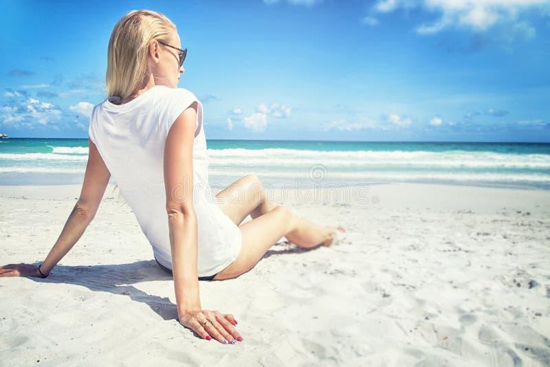 De jonge zitting van de blondevrouw op het strand stock afbeelding