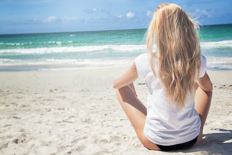 De jonge zitting van de blondevrouw op het strand royalty-vrije stock afbeelding