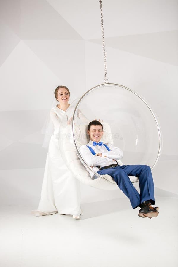 De jonge zitting van de bruid slingerende bruidegom als bellenvoorzitter stock afbeelding