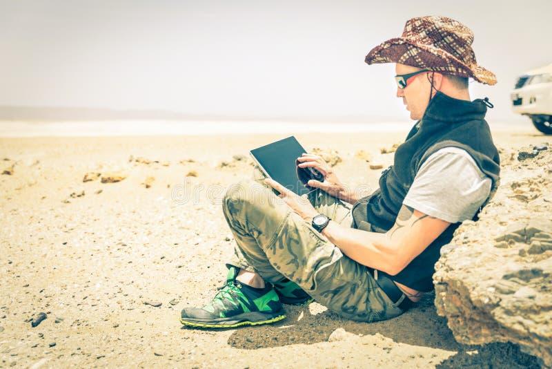 De jonge zitting van de hipstermens in woestijnweg - Technologieconcept stock fotografie