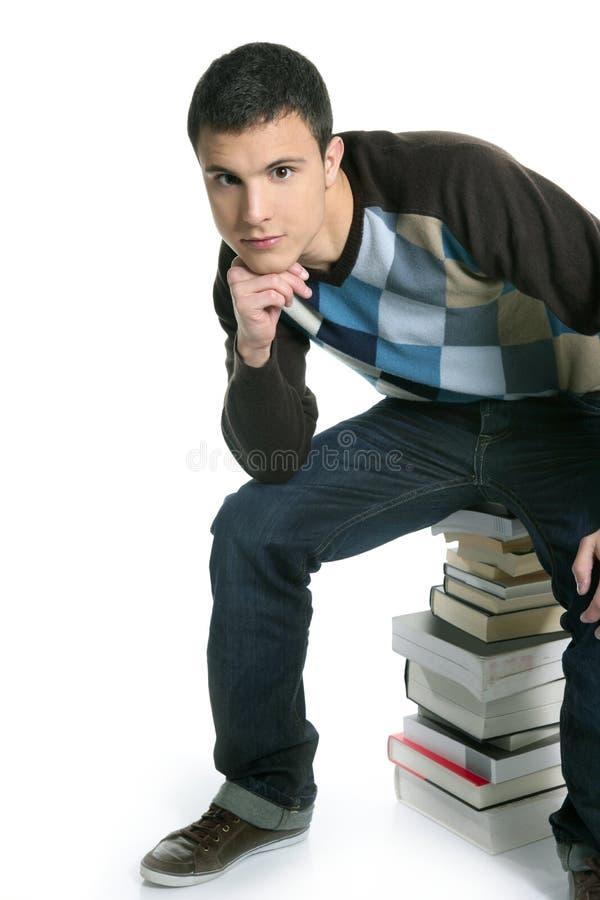 De jonge zitting van de studentenjongen over stapelboeken royalty-vrije stock afbeelding