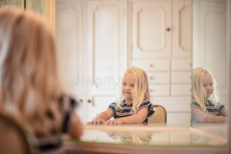 De jonge zitting van het blondemeisje bij ijdelheidsspiegel in kleedkamer ziet eruit royalty-vrije stock foto