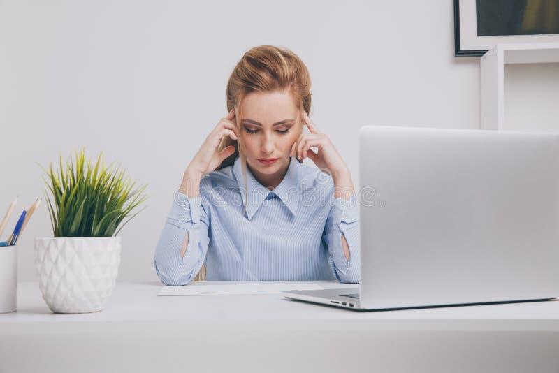 De jonge zitting van het bureaumeisje op het haar werk die slecht voelen De vrouw heeft een hoofdpijn stock foto