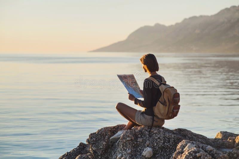 De jonge zitting van het reizigersmeisje met kaart dichtbij het overzees bij zonsondergang, reis, wandeling en actief levensstijl stock afbeeldingen