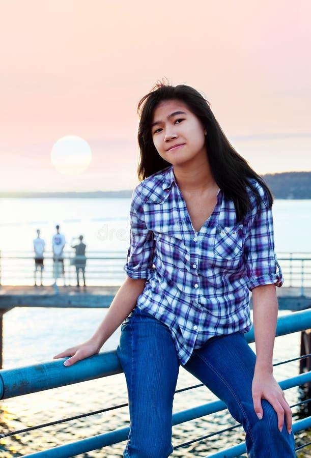 De jonge zitting van het tiener biracial Aziatische meisje op metaaltraliewerk door meer royalty-vrije stock foto