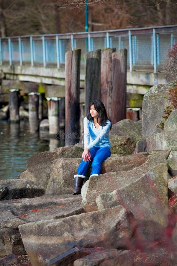 De jonge zitting van het tienermeisje op grote keien langs meerkust, die uit over water kijken stock afbeeldingen
