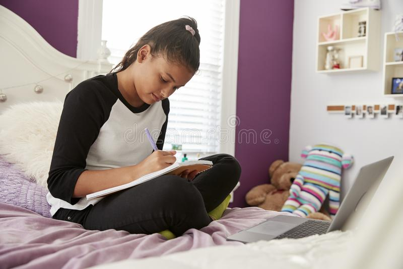 De jonge zitting van het tienermeisje op haar bed die in een notitieboekje schrijven stock afbeeldingen