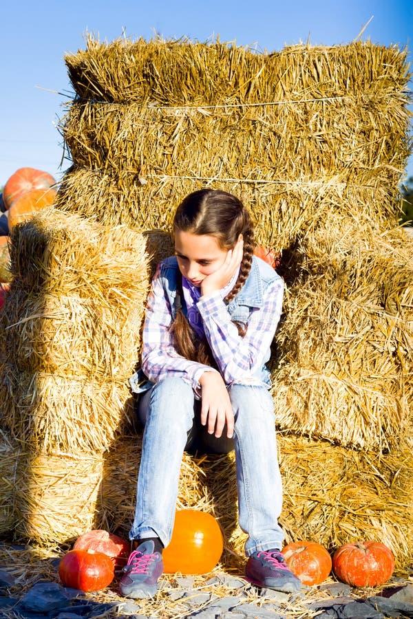 De jonge zitting van het tienermeisje op stro met pumkins op landbouwbedrijfmarkt Familie het vieren dankzegging of Halloween royalty-vrije stock foto's