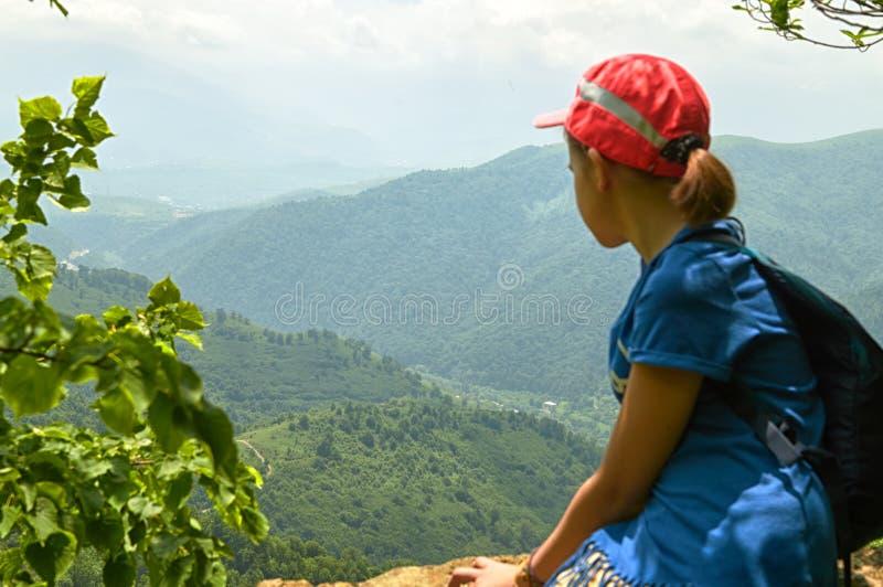 De jonge zitting van het wandelaarmeisje op de hoge klip in Armeense bergen in zonnige de zomerdag stock afbeelding