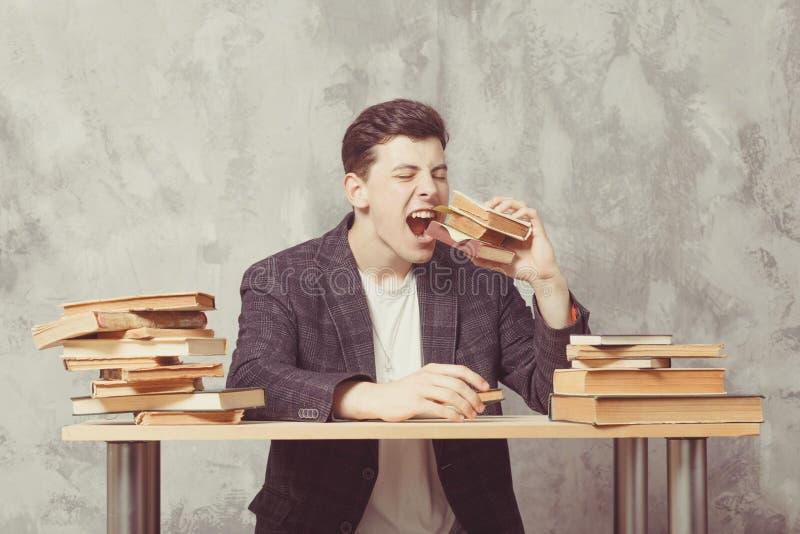 De jonge zitting van de jongensstudent dichtbij de lijst met boeken in glazen De kerel wil lerend, heeft onderwijs Online Onderwi stock fotografie